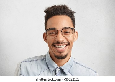 Horizontal portrait of happy male enterpreneur being glad to succeed in marketing development, expresses positive emotions and feelings, isolated over white studio background. Facial expressions