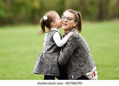 horizontal portrait of a little girl in a gray dress with white blouse hugging and kissing her mom in the park in spring