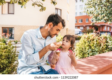 Horizontal portrait of little girl sitting with dad on the street and eating ice-cream outdoor. Happy kid wears dress spending time together with father. Good relationship between dad and daughter