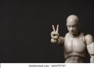 A horizontal portrait of mannequin showing v-sign against black background