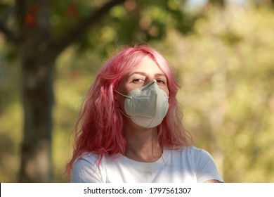 horizontal portrait of modern woman with loose pink hair and medical mask looking defiantly to camera on a natural green background