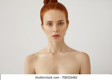 Horizontal portrait of naked beautiful female with freckled healthy skin and ginger hair tied in knot, looking with her green eyes and slightly oprnrf mouth into camera, having mysterious look