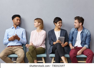 Horizontal portrait of people sit in queue, have pleasant conversation with each other, share ideas and life experience, isolated over grey concrete wall. Diverse group in row, speak and hold gadgets
