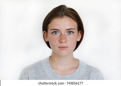 Horizontal portrait of pleasant-looking Caucasian female  with chestnut hair and freckles on her face expressing calm emotions. Portrait of a girl with freckles. People and lifestyle concept.