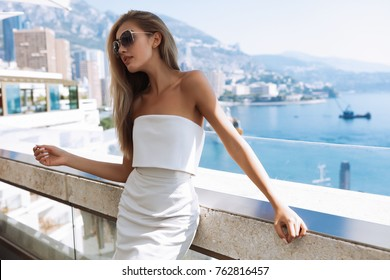 Horizontal portrait of pleasant-looking Caucasian female with healthy long hair,copy space,nails,wearing white casual dress, enjoy her morning coffee,looking happily in camera,glasses.Monte Carlo