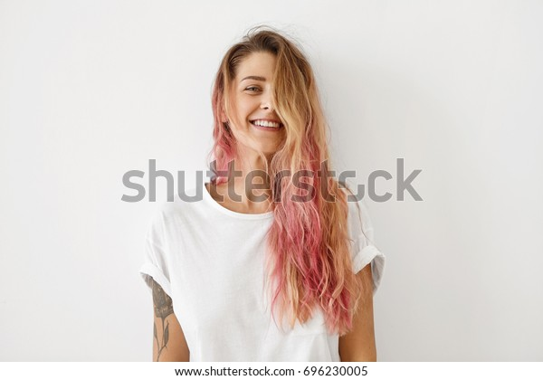 Horizontal portrait of pleasant-looking Caucasian female with long hair, pink on tips, having tattooes on arms, wearing white casual T-shirt, covering her face with hair, looking happily in camera