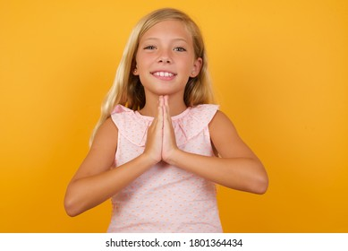 Horizontal portrait of pretty blonde little girl keeps palms together, has pleased expression. Glad attractive female makes request, pleads for mercy. Hopeful young adult.