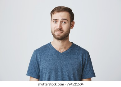 Horizontal portrait of puzzled and confused man with beard dressed casually, looking at camera with his blue eyes, thoughtful, not knowing what is wrong. Human feeling, emotions, face expressions