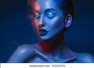 Horizontal portrait of sensual woman in blue body art in studio