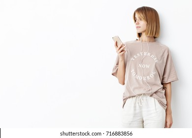 Horizontal portrait of slim young female stands sideways, looks pensively into distance, listens to audio on smart phone app for fitness motivation. Female sport trainer rests after training
