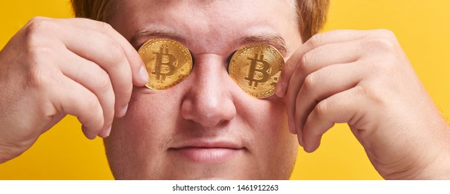 Horizontal portrait of smiling fat man with bitcoins in the eyes on yellow background. Concept of virtual digital money, greed, vanity, wealth and stinginess