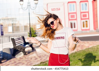 Horizontal portrait of a standing widely smiling and dancing young girl holding a smartphone and listening to music. Girl wears a white t-shirt, red skirt and dark sunglasses.