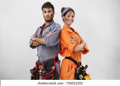 Horizontal portrait of successful hard working young female and male technicians work as friendly team, stand backs, rejoice finishing working day, managed to do much things and repair many objects