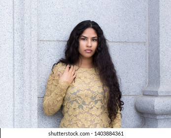 Horizontal portrait of sultry hispanic young woman with long curly dark hair wearing elegant gold lace top leaning against stone wall with right hand against chest