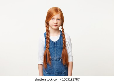 Horizontal portrait of tender little blue-eyed child girl with freckles and braided in two long plaits red hair, stands calmly looking camera, in jeans overall dress isolated on white background