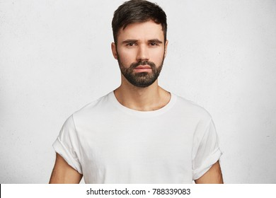 Horizontal portrait of unshaven stylish young man dressed in white new t shirt, looks seriously directly in camera, expresses his confidence, rests at home after hard working day, isolated on white