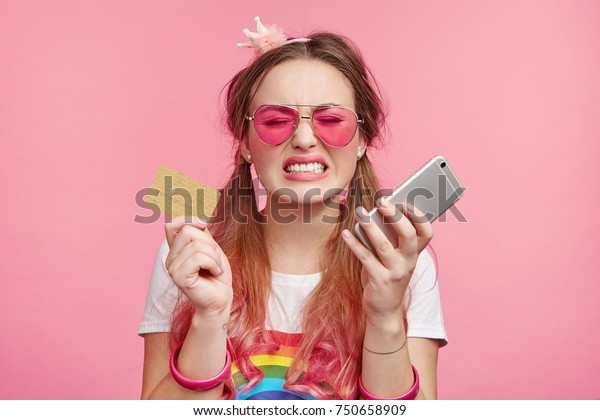 Horizontal portrait of upset miserable woman wears trendy sunglasses, holds plastic card and mobile phone, being short of money, can`t buy new clothes or cosmetics, has bad mood. Online shopping