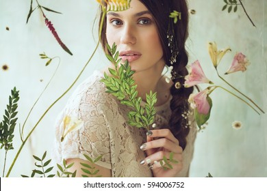 Horizontal portrait of woman behind the screen with flowers and plant in hand