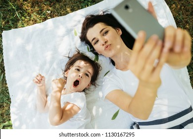 Horizontal portrait of young beautiful woman mother blowing kiss and taking self portrait with her cute kid lying on green grass and white blanket. Motherhood, technology and childhood concept.