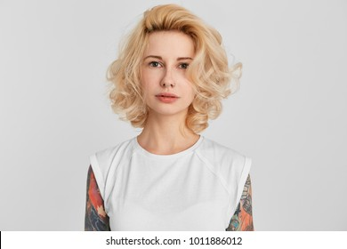Horizontal portrait of young blond girl, wearing a white casual t-shirt, pierced nose standing straight and thinking. Serious. Isolated on white wall