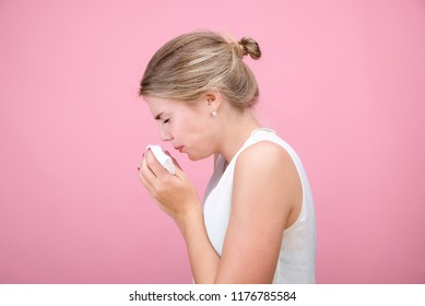 Horizontal portrait young blonde girl with a handkerchief and runny nose in profile, looking into the camera, white skinned female model at pink wall isolated.