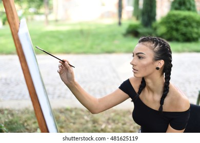 horizontal portrait of a young brunette woman with braided pigtails sitting and painting in the park with a canvas in front of her, with blurred bushes and trees in the background