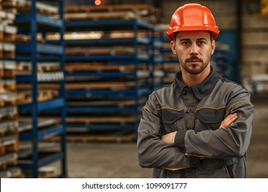 Horizontal portrait of a young male metalworker in protective hardhat and uniform posing confidently at the warehouse of a industrial manufacturing. Confidence, success, business concept