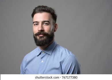 Horizontal portrait of young successful stylish bearded businessman with copyspace against gray studio background.