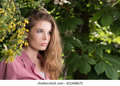 Horizontal portrait of a young woman with her hair beneath a flowered tree. Casual wear