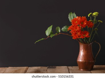 A horizontal presentation of a copper vase with a bouquet of bright colored flowers on a black background and a wooden table.