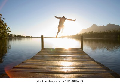 Horizontal rear view of a man leaping from a jetty into the lake at sunset.