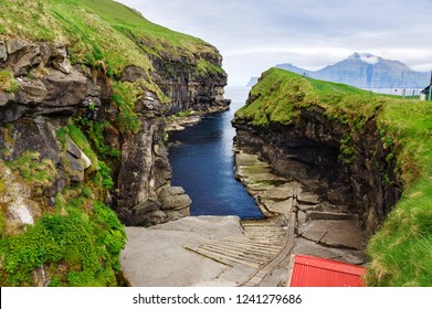 Horizontal scenery image of natural harbour gorge nearby idyllic village Gjogv, most northern village of Eysturoy, Faroe islands