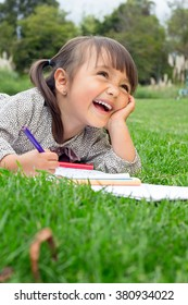 Horizontal shot of 4 year old girl drawing and smiling on the park.