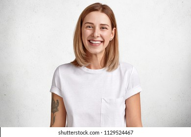 Horizontal shot of adorable Caucasian female with positive expression, has white perfect teeth, healthy skin, tattoo on arm, short hair rejoices good news, poses against white concrete wall.