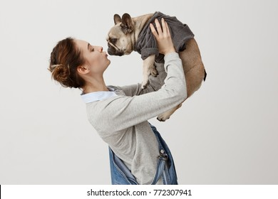 Horizontal shot of adult girl in jeans overalls kissing cute puppy while raising it in air. Young girl being in love with her dog clothed in trendy jumper. Display of affection