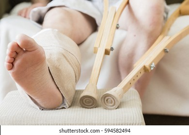 horizontal shot of an adult male with his leg in a cast and bandaged up on a foot stool with crutches lying beside him.