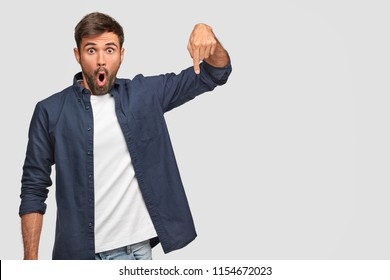 Horizontal shot of amazed man with stupefied expression, points down with index finger, dressed in casual clothes, shows free space for your advertising content. Astonished young Caucasian man