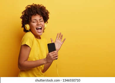 Horizontal shot of amused joyful dark skinned lady listens new song from internet radio website, sings, gestures and closes eyes, has relaxation time, isolated over yellow studio wall with empty space