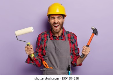 Horizontal shot of annoyed stressful builder shouts from anger, poses with building tools in workwear, has irritated face expression, isolated over purple wall. People, maintenance, repairing concept