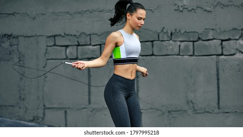 Horizontal shot of athelete determined woman skipping with rope outdoors next the cocnrete wall. Fitness female exercising with jump rope outside on a sunny day.