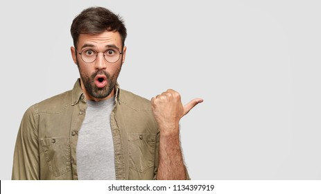 Horizontal shot of attractive amazed unshaven European male in fashionable shirt points aside with thumb, shows something against white blank wall, has shocked expression. Let`s go in this direction