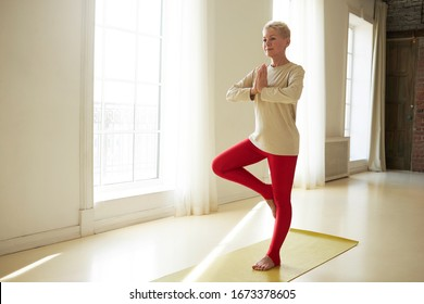 Horizontal shot of attractive retired European female wearing red leggings and long sleeved shirt keeping hands clasped and one feet on knee, doing tree pose while practicing yoga on mat at home