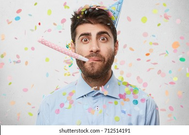 Horizontal shot of attractive unshaven young man wearing formal shirt and cone hat on his head looking in surprise, blowing party horn. People, joy, birthday, anniversary, fun and party concept