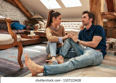 Horizontal shot of an attractive young couple talking in the living room