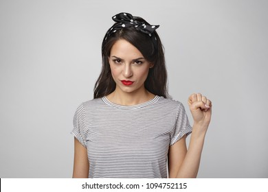 Horizontal shot of attractive young woman feminist wearing bright make up and headscarf having confident look, raising clenched fist as sign of feminism, equal rights, respect and girl power