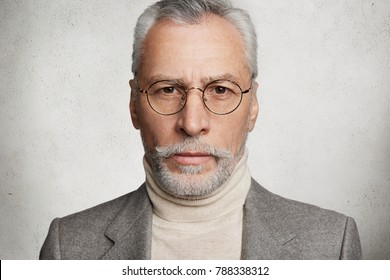 Horizontal shot of bearded confident male wears suit and round spectacles, isolated over white background. Serious mature businessman poses against white concrete wall indoor. Age and people concept