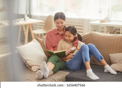 Horizontal shot of beautiful Asian woman relaxing on sofa with her lovely daughter reading interesting novel
