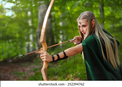 Horizontal shot of a beautiful blonde haired woman elf hunting in the forest with a bow and arrows copyspace fantasy fairytale magic hunter archery archer weapon nature woods cosplay costume movie.