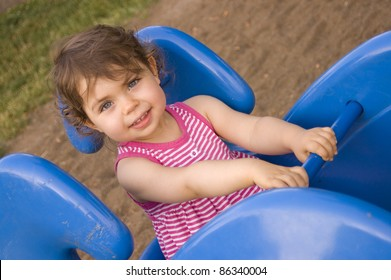 Horizontal shot of a beautiful Caucasian toddler girl riding a blue playground spring toy; model released.