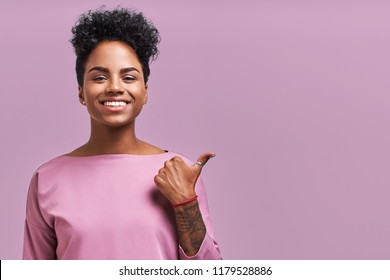 Horizontal shot of beautiful female with dark skin keeps mouth opened, wears casual lavender clothes, indicates at blank space with thumb, has stupefied expression. People, ethnicity concept.